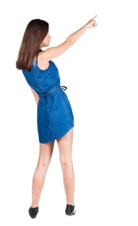 Vista posterior de la mujer que se�ala. hermosa chica morena en el vestir. Vista posterior recogida de las personas. trasero vista de la persona. Aislado sobre fondo blanco. photo