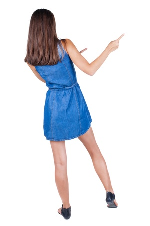 Back view of young brunette woman pointing at wall. cheerful girl in dress. Rear view people collection. backside view of person. Isolated over white background. photo