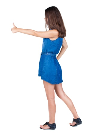 Back view of successful woman thumbs up. Rear view people collection. backside view of person. Isolated over white background. slender brunette in a dress shows hitchhiking photo