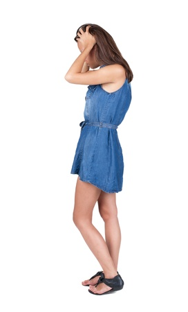 Back view of shocked woman in blue dress. girl hid his eyes behind his hands.  Rear view people collection.  backside view of person.  Isolated over white background. photo