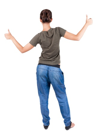 Back view of  woman thumbs up. Rear view people collection. backside view of person. Isolated over white background. slender brunette in a jeans shows the symbol of success or hitchhiking photo