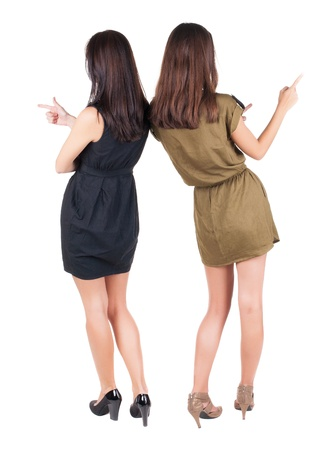back view of businessteam. two young  business woman in dress pointing.  Rear view people collection.  backside view of person.  Isolated over white background. photo