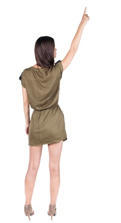 Back view of  pointing woman. beautiful brunette  girl in dress. Rear view people collection.  backside view of person.  Isolated over white background.