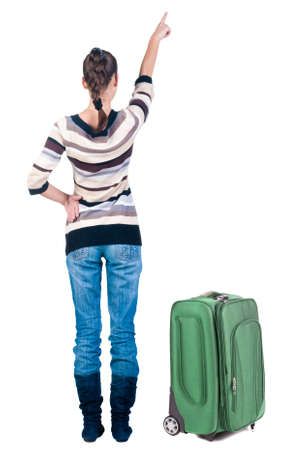 traveling young woman with suitcas  pointing at wall. Back view people. Stock Photo - 22344349