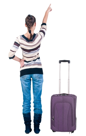 traveling young woman with suitcas  pointing at wall. Back view people. Stock Photo - 22344357