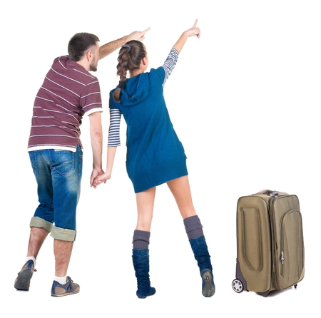 Young traveling couple with suitcas looks where that. Back view people. Isolated over white. Stock Photo - 22363014