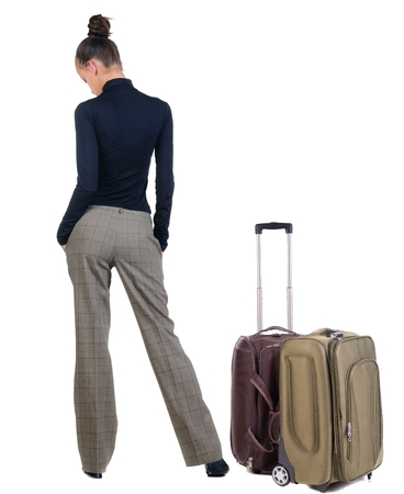 traveling sad young woman with suitcas . Back view people. isolated over white photo
