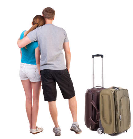 Back view of young traveling couple with suitcas.  Rear view. Isolated over white background. Sports heterosexual couple hugging in summer shorts photo