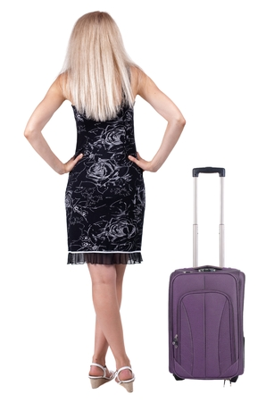 back view of standing young traveling blonde woman with suitcas. girl  watching. Rear view people collection.  backside view person.  Isolated white background.  photo