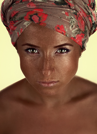 portrait of tanned girl in a turban. dark-skinned woman with freckles photo