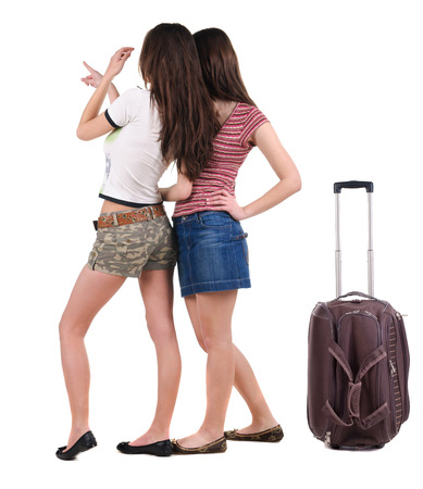 Two young women traveling with suitcas rear view. Isolated over white. photo