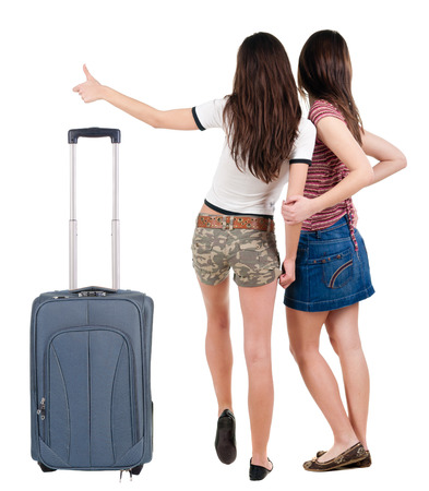 Two young  women friends traveling with suitcas and showing thumbs up.  backside view of person. Isolated over white background. Rear view people collection.  photo
