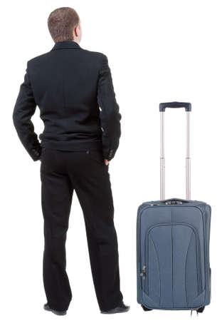 back view of adult man in black suit  traveling with suitcase.