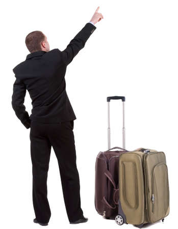 back view of adult man in black suit  traveling with suitcase. photo