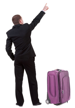 Back view of pointing business man traveling with suitcas . gesticulating young guy in black suit. Rear view people collection.  backside view of person.  Isolated over white background. photo