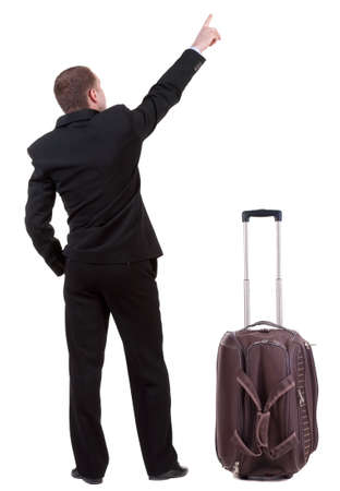 Back view of pointing business man traveling with suitcase , gesticulating young guy in black suit. photo