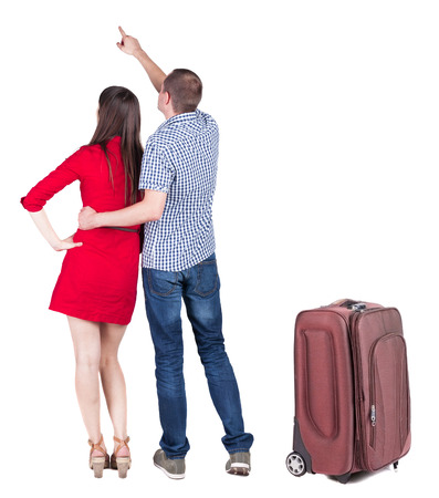 young couple traveling with suitcase and pointing at wall. Stock Photo - 23164510