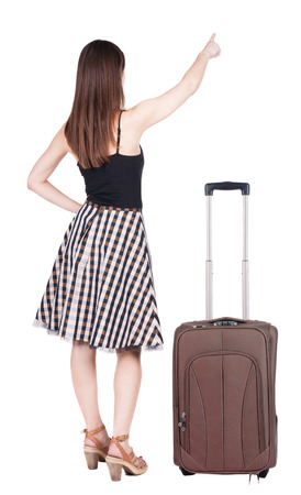 Back view of young brunette woman traveling with suitcase and pointing at wall. photo