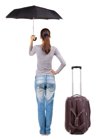 back view of woman with umbrella traveling with suitcase. photo