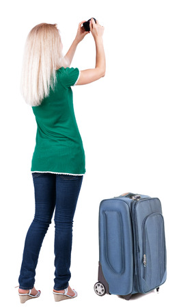 Back view of woman photographing traveling with suitcase. Stock Photo