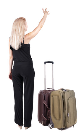 Back view of young blonde woman traveling with suitcase and pointing . Stock Photo - 23169777