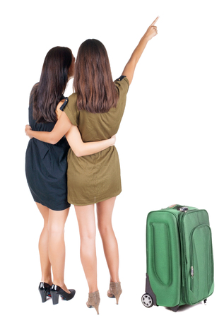 back view of businessteam traveling with suitcas. two young  business woman pointing.  Rear view people collection.  backside view of person.  Isolated over white background. photo