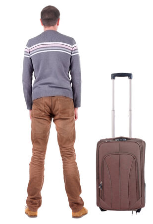 Back view of young man traveling with suitcase.  photo