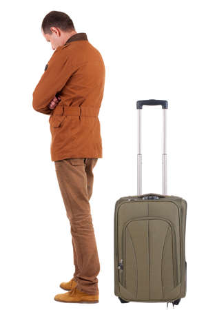side view of young man traveling with suitcase. photo