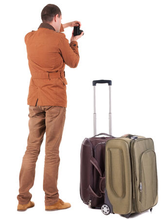 Back view of man photographing traveling with suitcase. photo