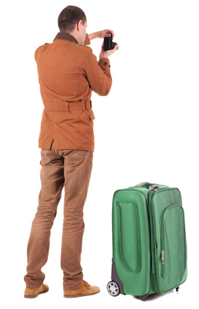 Back view of man photographing traveling with suitcase.  Rear view people collection.  backside view of person.  Isolated over white background. photo