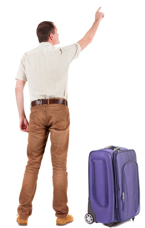 Back view of  pointing young men traveling with suitcase.  photo