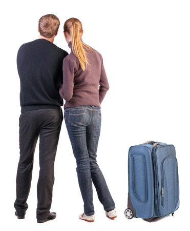 Back view of young couple traveling with suitcase. photo