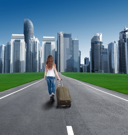 Rear view of a girl with a suitcase entering the city. Tourist returns home. The man moved to the new location. globalization. concept photo