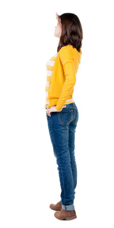 back view of standing young beautiful  brunette woman in yellow pullover. girl  watching. Rear view people collection.  backside view of person.  Isolated over white background. Stock Photo