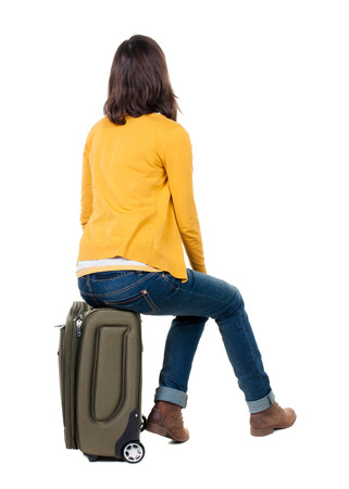 espalda: Vista posterior de la mujer que camina en rebeca sienta en una maleta. hermosa chica en movimiento. trasero vista de la persona. Vista posterior recogida de las personas. Aislado sobre fondo blanco.