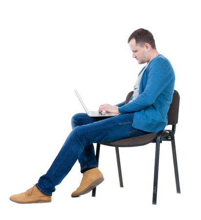 Side view of a man sitting on a chair to study with a laptop. Isolated  over white background photo