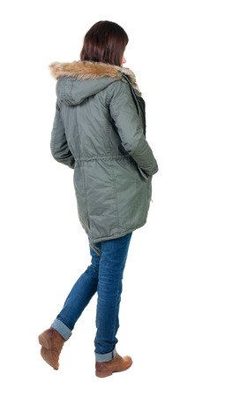 back view of standing young beautiful  brunette woman in park. girl in warm jacket  watching. Rear view people collection.  backside view of person.  Isolated over white background. photo