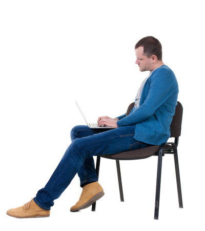 Side view of a man sitting on a chair to study with a laptop.  photo