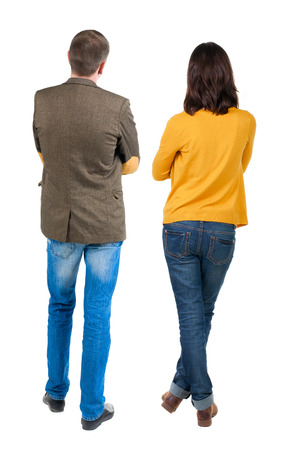 Back view of young couple (man and woman) hug and look into the distance. beautiful friendly girl and guy together.