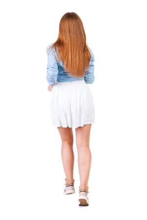 back view of running  woman in dress. beautiful redhead girl in motion. backside view of person.  Rear view people collection. Isolated over white background. photo