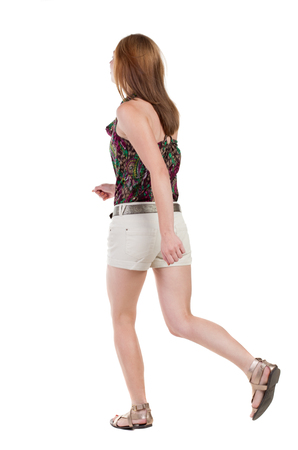 back view of running  woman. beautiful redhead girl in motion. backside view of person.  Rear view people collection. Isolated over white background. photo