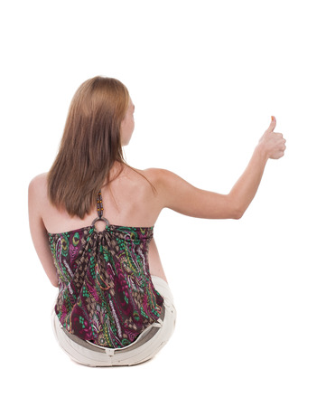 back view of siting young blonde  woman showing thumb up.  Rear view people collection.  backside view of person.  Isolated over white background photo