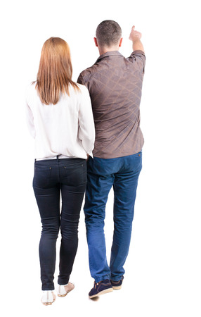 Back view of walking young couple (man and woman) pointing. Rear view people collection. backside view of person. Isolated over white background Imagens - 31235060