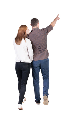 Back view of walking young couple (man and woman) pointing. Rear view people collection. backside view of person. Isolated over white background Standard-Bild