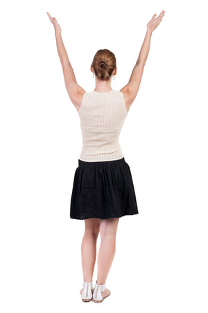 Back view of Beautiful woman in dress looking at wall and Holds  hand up.  young blonde girl standing. Rear view people. Isolated over white background.  photo