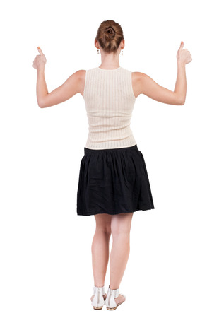 Back view of successful woman thumbs up. Rear view people collection. backside view of person. Isolated over white background. slender blonde in a dress shows hitchhiking photo