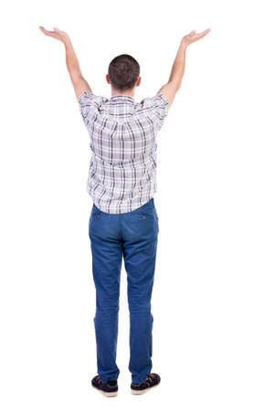Back view of Beautiful man in jeans looking at wall and Holds  hand up.  young brunette standing. Rear view people. Isolated over white background.  photo