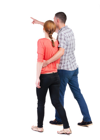 Back view of walking young couple (man and woman) pointing. Rear view people collection. backside view of person. Isolated over white background photo