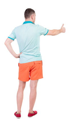 Back view of  man in shorts shows thumbs up.   Rear view people collection.  backside view of person.  Isolated over white background. photo