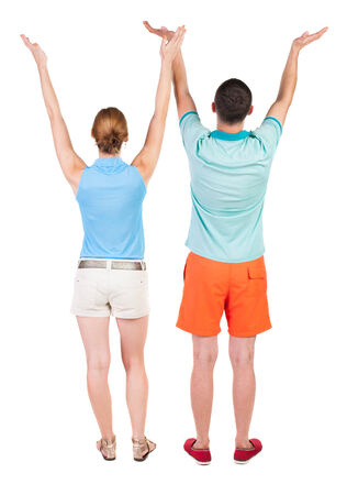 Back view couple  looking at wall and Holds  hand up. Rear view people. Isolated over white background.  photo